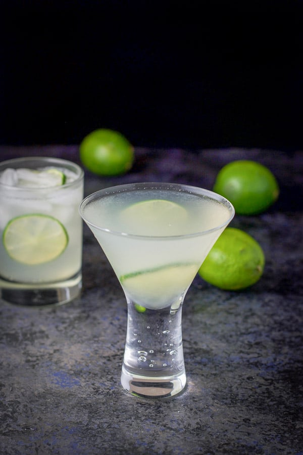 The gimlet is in the bubble martini glass with the double old fashioned behind it and 3 limes on the table