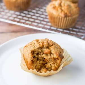 Close up of a white plate with one of the muffins with a bite taken out of it. There are more muffins in the background on a rack - square