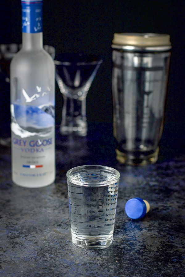 Vodka poured out for the drink with the bottle in the background