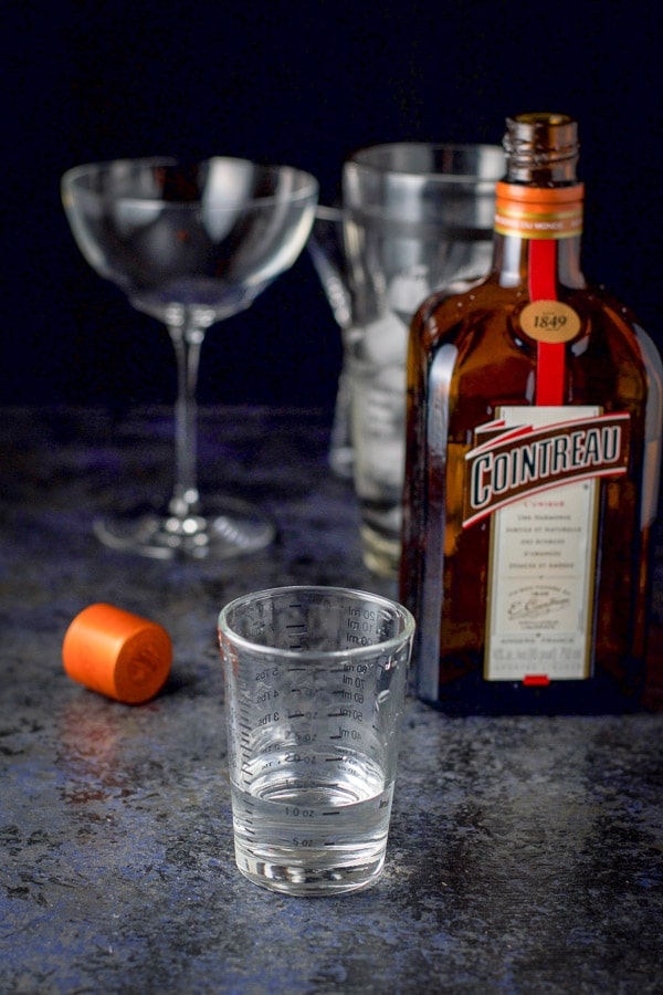 Cointreau measured out for the cosmo with the bottle in the background