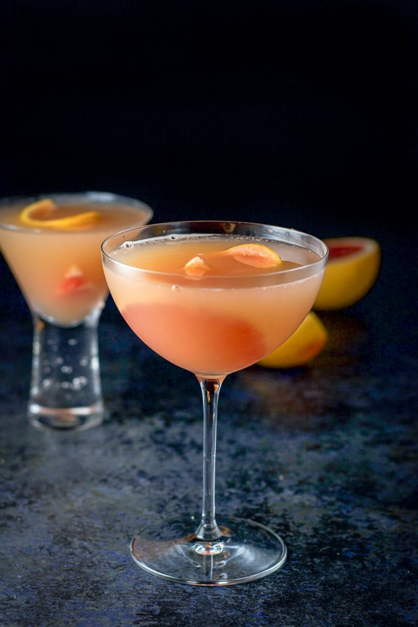 A bowl shaped glass of the cosmo in front with a bubble glass of in the background