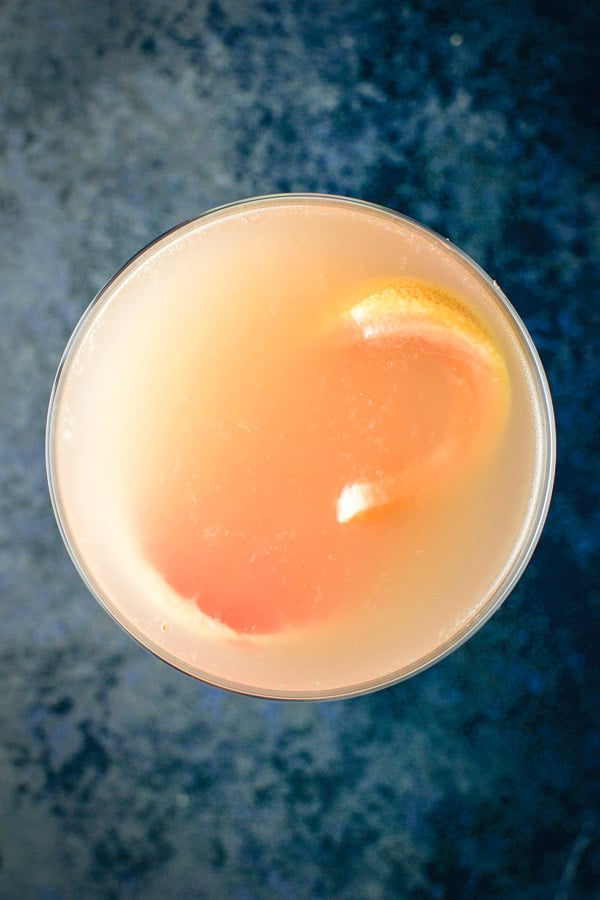 Overhead view of the ruby red grapefruit cosmo with a thin slice of grapefruit floating in the glass