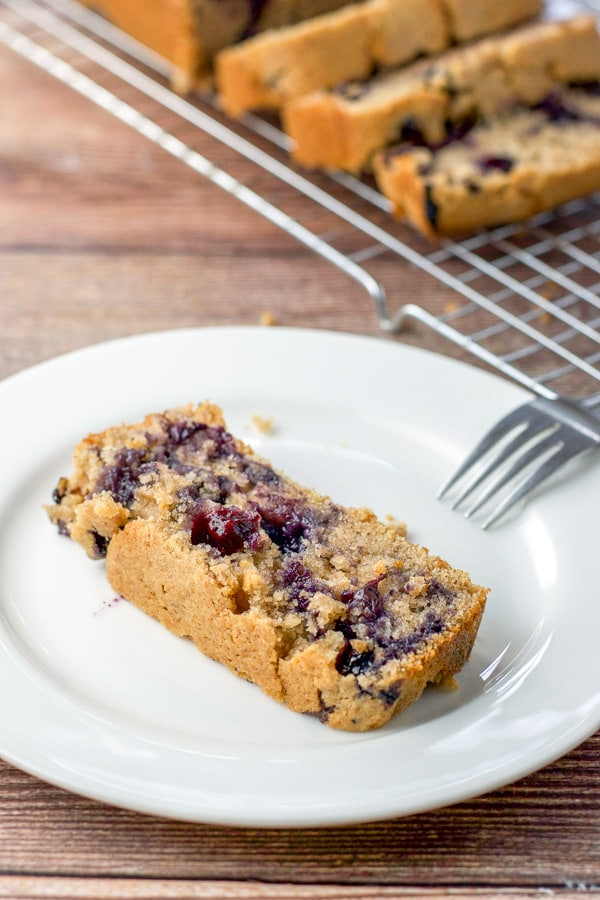 A piece of lemon blueberry bread on a plate with a few pieces on a wire rack behind it