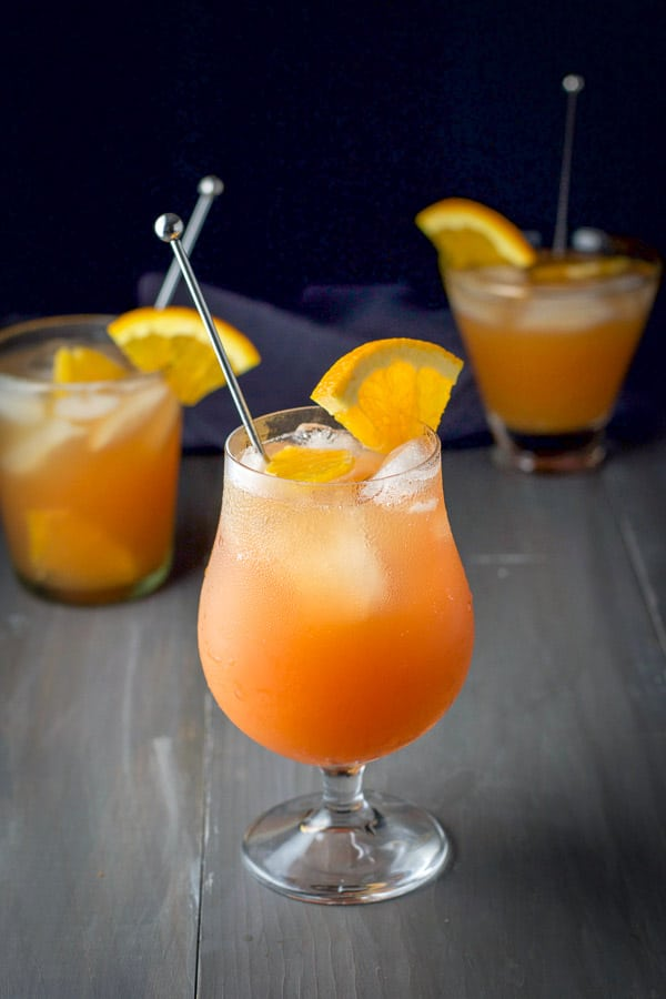 A tulip glass filled with the orange rum drink in front of two other glasses. They all have orange slices and garnish