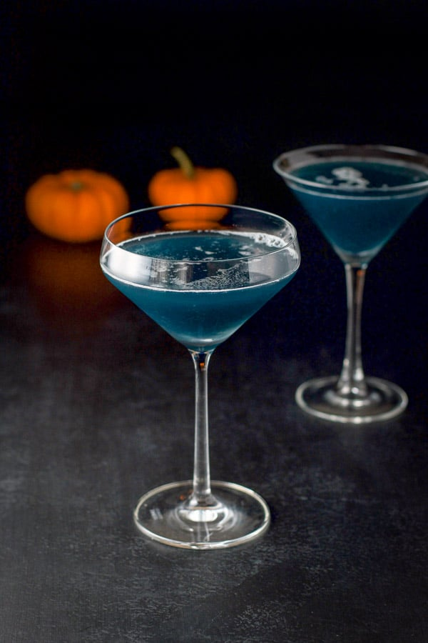 The witches cocktail in two martini glasses, one with a bevel and the other a classic glass.