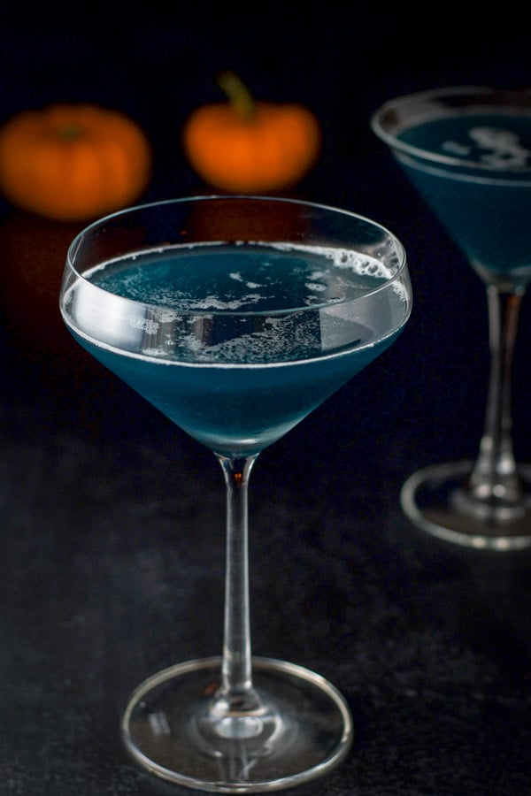 Close up of the curved glass filled with the blue cocktail in front of the classic martini glass in back with two small pumpkins