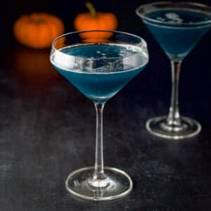 Curved glass filled with the blue witches cocktail with a classic glass behind it - square
