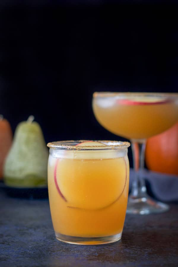 Vertical view of the short glass filled with the apple margarita with the apple round in it and the taller glass behind it