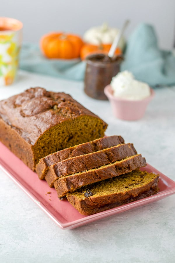 Four slices of pumpkin bread and the remaining loaf on a pink serving plate with cream cheese ad prune spread in background