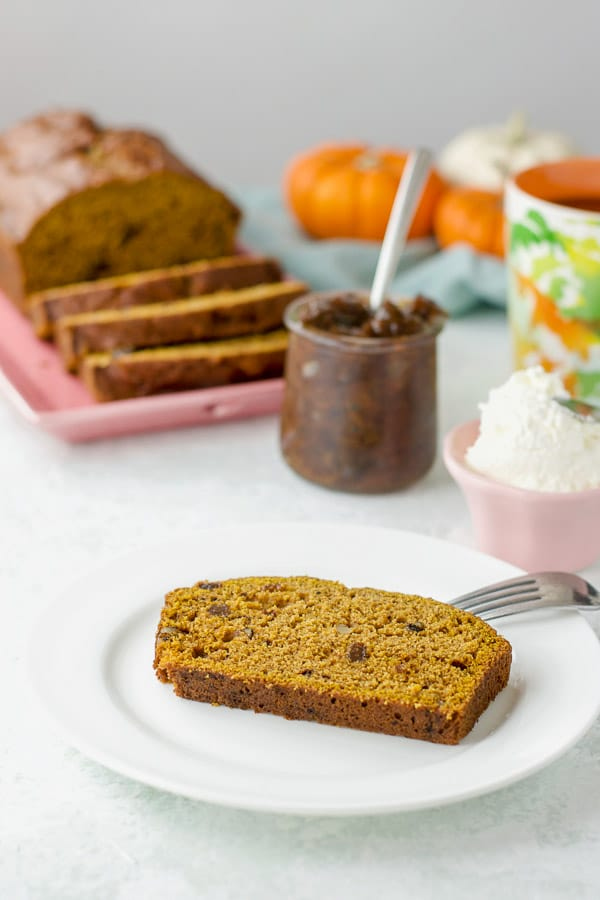 A slice of plain pumpkin bread on a plate with cream cheese, prune spread and the rest of the loaf in the background
