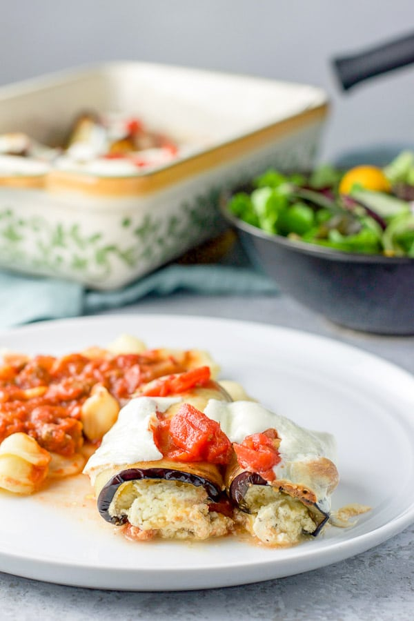 A white plate with ricotta oozing out of rolled up eggplant with pasta on it as well. There is the baking dish and a salad in the background
