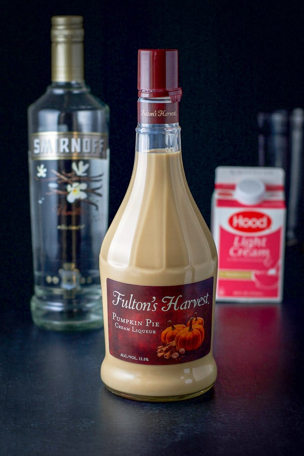 Pumpkin spice liqueur, vanilla vodka and light cream on a black table