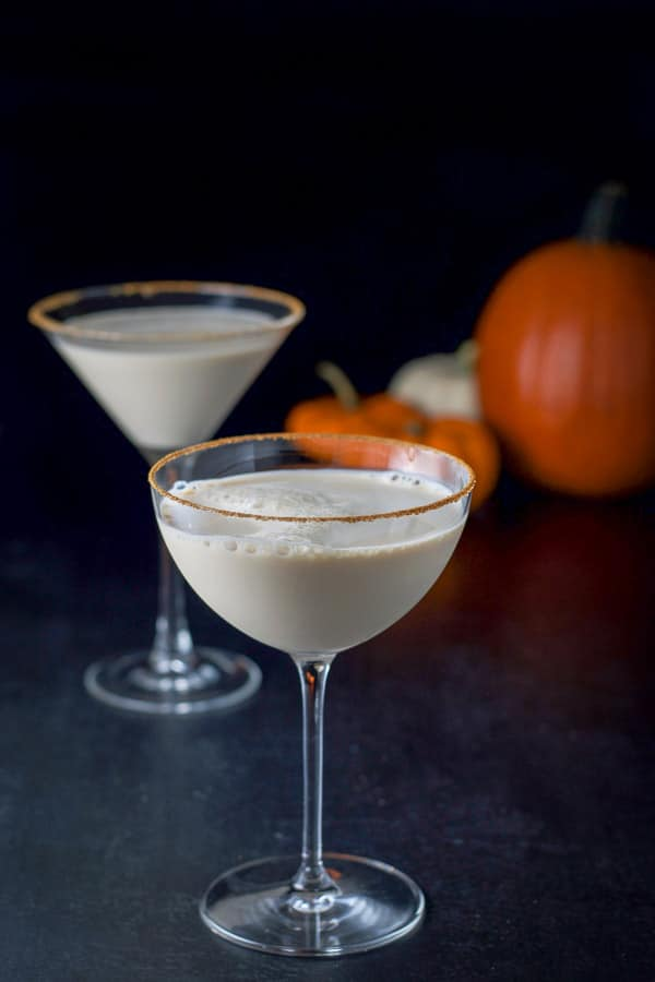 Bowl glass filled with pumpkin martini with the classic martini glass in back with some pumpkins