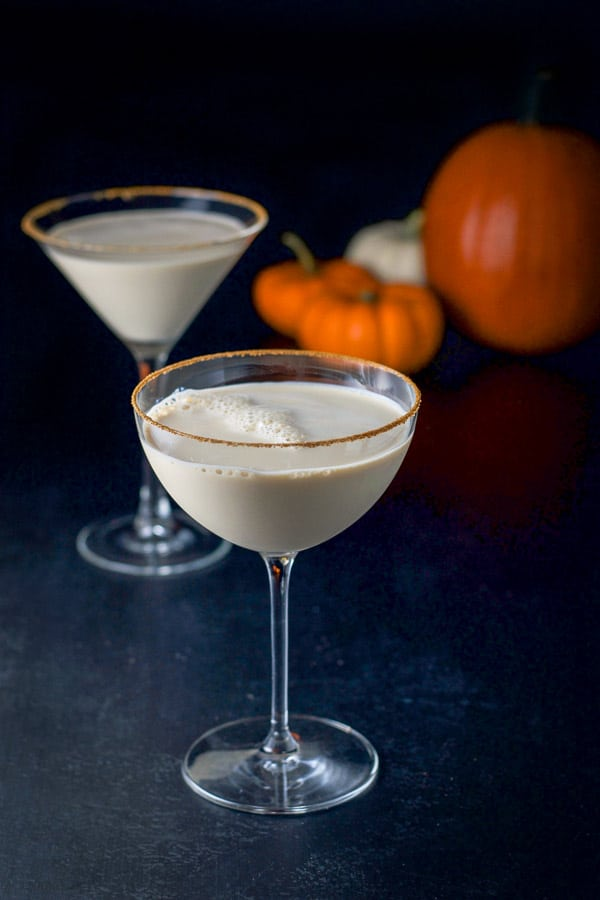 Cinnamon sugar lined martini glasses with the martini with pumpkins in the background