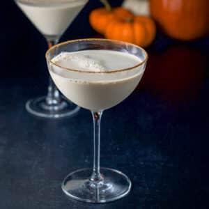 Cinnamon sugar lined martini glasses with the pumpkin martini. There are pumpkins in the background - square