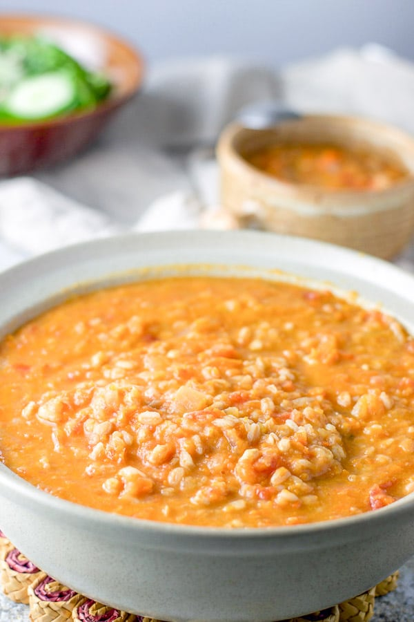 Farro cooked and the bean soup is in a serving bowl. There is a crock of soup and a salad behind it