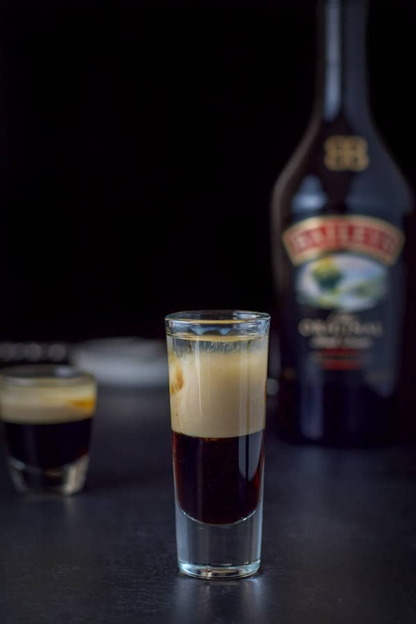Baileys layered into the glass with the bottle in the background along with a white dish and spoon