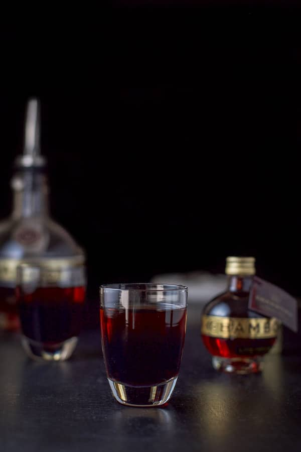 Chambord layered into the shot glasses with the bottle in the backgound