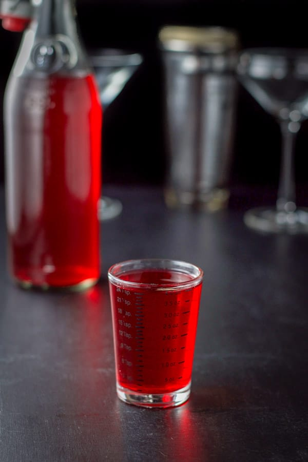 Cranberry vodka poured out with the bottle in the background along with the glasses and shaker
