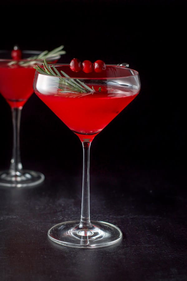 Cranberry cocktail in two martini glasses with the curved glass in front and garnished with cranberries and fresh rosemary