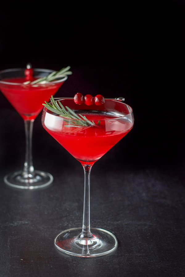 Fun curved martini glass filled with the red cosmo with fresh rosemary as a garnish along with some cranberries on a pick