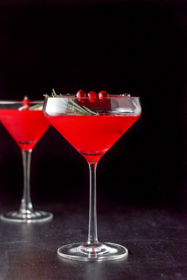 Vertical view of the cosmo with cranberries and rosemary as garnish