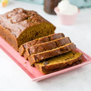 pumpkin bread on a pink plate sliced in pieces - square