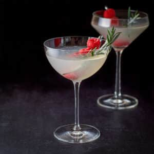 Bowl and curved martini glasses filled with the festive cocktail with raspberries and rosemary in as garnish - square