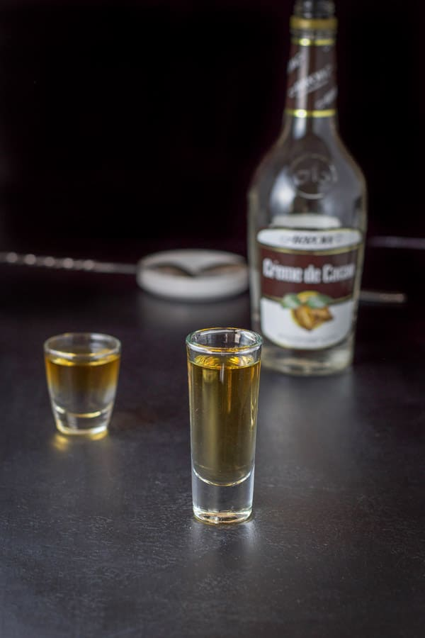 Creme de Cacao layered in the glasses with the bottle in the background
