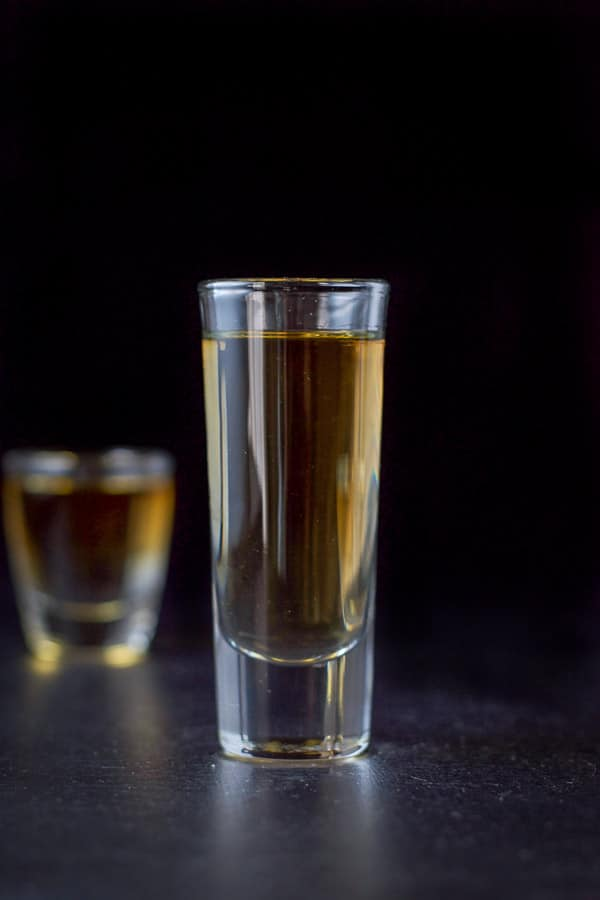 Vertical shot of the amber shot. The tall glass in front of the short glass