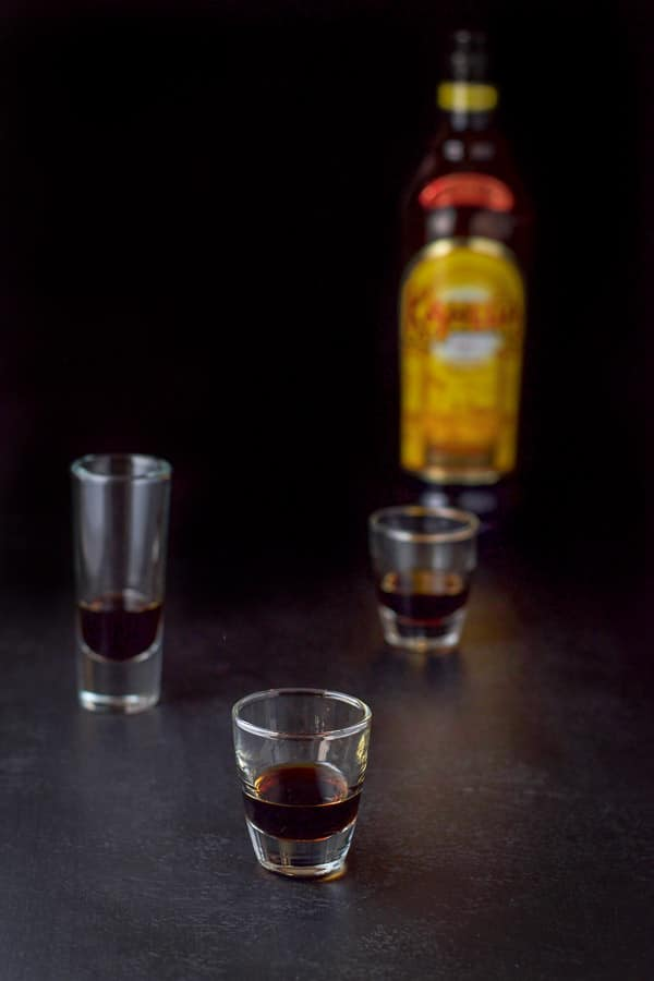 Kahlua poured in the shot glasses with the bottle in the background