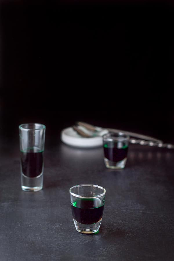 Creme de menthe layered in the glasses with the spoons and white bowl behind them