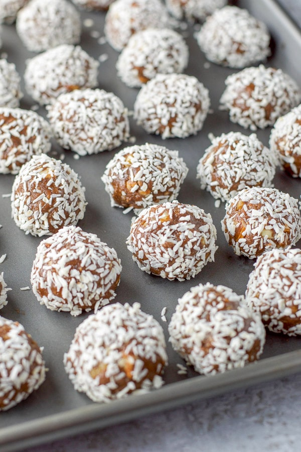 Amaretto Balls formed and dipped in flaked coconut on a jelly roll pan