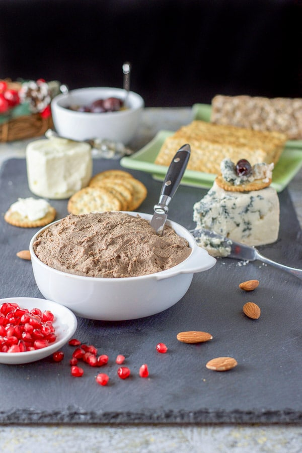 A white bowl filled with pate, pomegranate seeds and lots of cheese in the background
