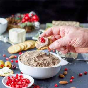 A male hand holding a cracker with liver pate on it with lots of crackers, cheese, pomegranate seeds and other appetizers - square