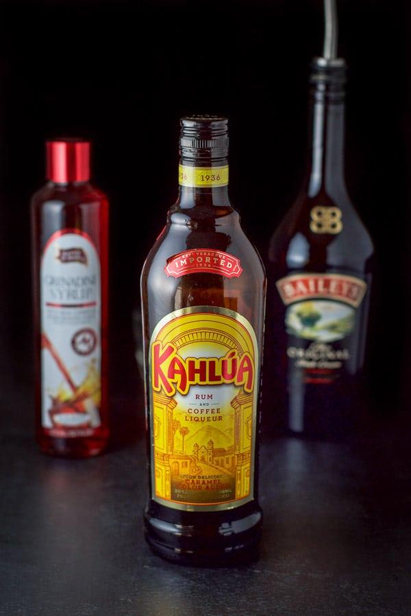 Kahlúa, Baileys and grenadine on a black table