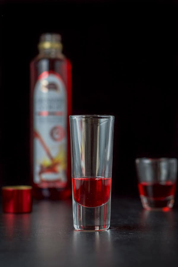 Grenadine poured into the shot glasses with the bottle in the background