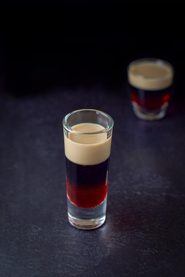 A clear view of the top of the glass of baileys, kahlua and grenadine, the tall glass in front of the shorter glass