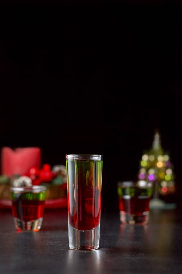 Vertical view of the tall glass filled with the green and red shot. There is a Christmas tree and candle in the background