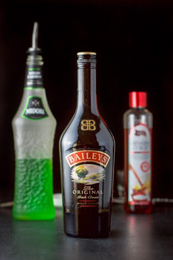 Baileys Midori and grenadine on a black board