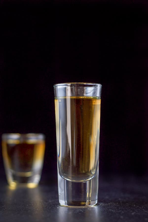 A short glass behind a tall glass filled with the layered shot