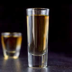 Tall glass filled with the amber shot - square