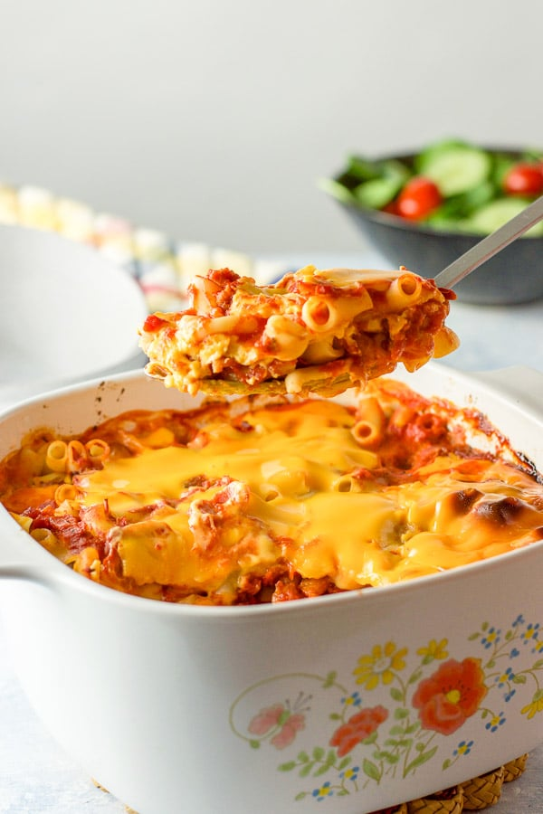 A big spoonful of pasta held over the casserole dish