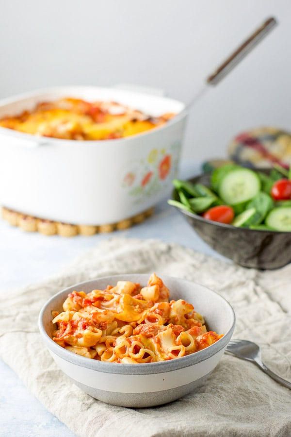 A bowl of pasta with a salad and the casserole dish in the background