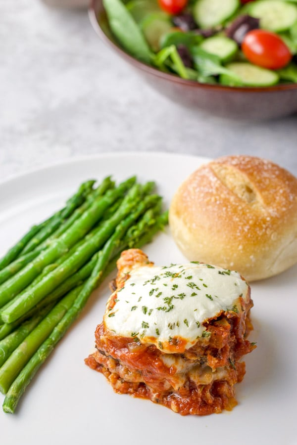 Serving of the eggplant parmesan on a plate with roll and asparagus spears
