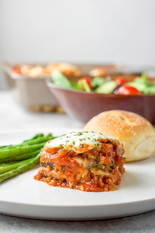 Almost vertical view of the baked eggplant parmesan with a roll on the plate