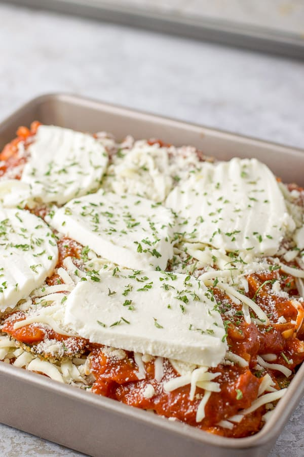 Sliced mozzarella and herbs on the eggplant parm