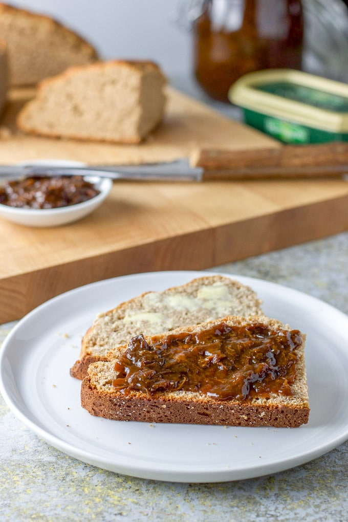 Prune spread on the soda bread in front and a piece with butter in the back