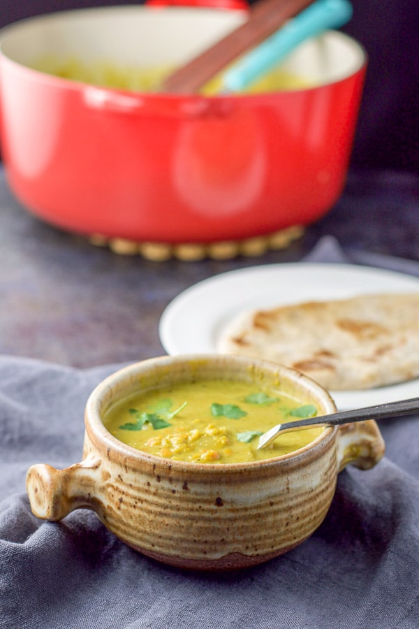 A crock full of lentil soup with naan on a white plate and the red pan in the background