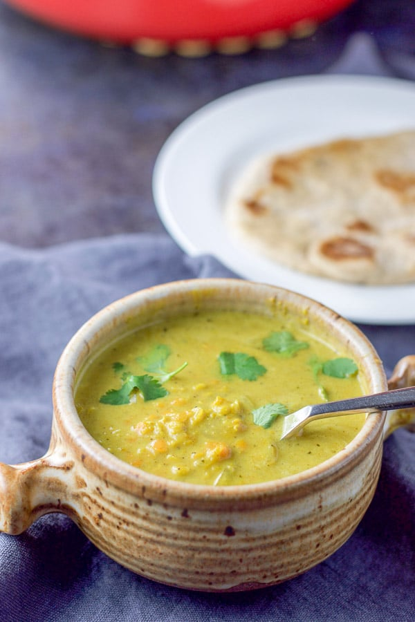 A close up view of the coconut lentil soup in a crock and some naan behind it